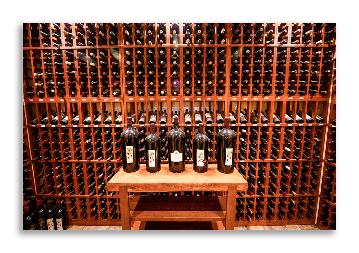 Image of a well-stocked and labeled wine cellar.