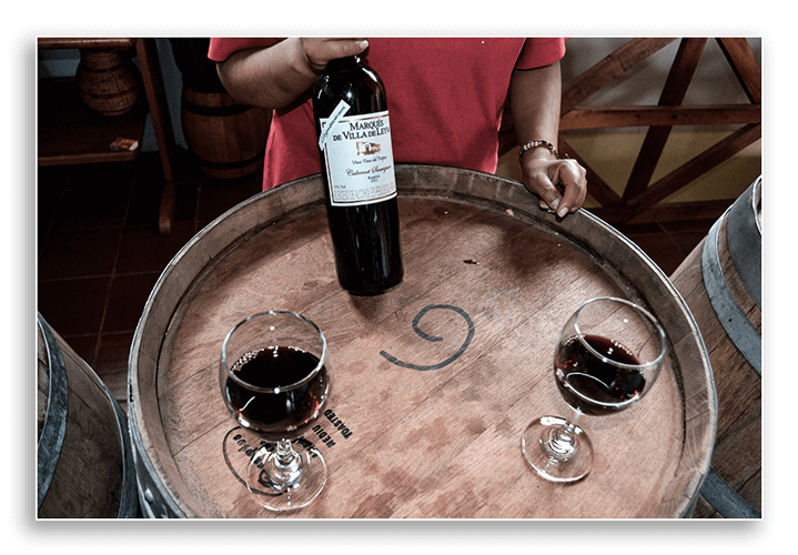 Image of red wine on top of a barrel.