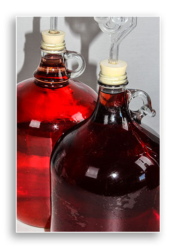 Image of two jugs of wine in storage.