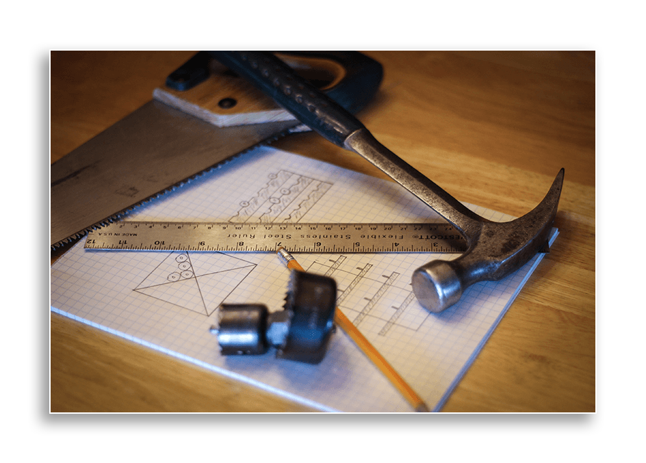 Image showing some hand tools laying on graph paper with wine rack sketches.