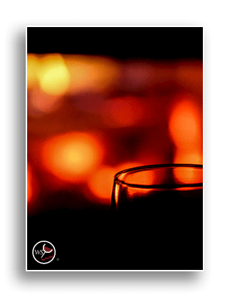 Image of a glass of wine in front of Christmas lights.